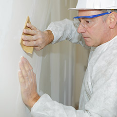 Man removing popcorn wall texture